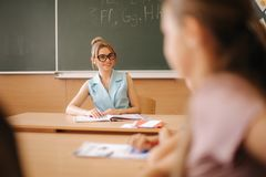 Pretty teacher in classroom sitting at the desk and asking children. education, elementary school, learning and people. Pretty teacher in classroom sitting at royalty free stock images