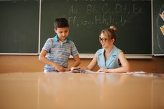 Pretty teacher in classroom sitting at the desk and asking children. education, elementary school, learning and people. Pretty teacher in classroom sitting at royalty free stock photo