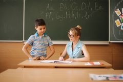 Pretty teacher in classroom sitting at the desk and asking children. education, elementary school, learning and people. Pretty teacher in classroom sitting at stock photos