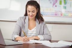 Pretty teacher correcting at her desk in a classroom Stock Photos