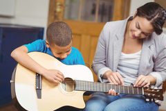 Pretty teacher giving guitar lessons to pupil Stock Photos