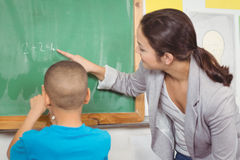 Pretty teacher helping pupil at chalkboard. In a classroom Royalty Free Stock Photos
