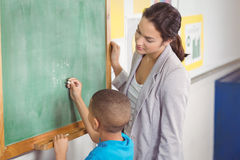 Pretty teacher helping pupil at chalkboard. In a classroom Royalty Free Stock Images