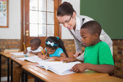 Pretty teacher helping pupil in classroom Royalty Free Stock Photo