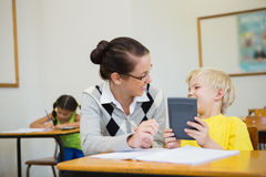 Pretty teacher helping pupil in classroom Stock Photo