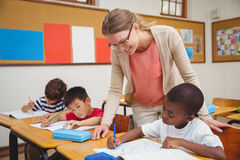 Pretty teacher helping pupil in classroom Royalty Free Stock Photos
