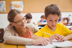 Pretty teacher helping pupil in classroom. At the elementary school Royalty Free Stock Images