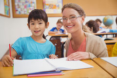 Pretty teacher helping pupil in classroom Royalty Free Stock Images