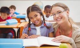 Pretty teacher helping pupil in classroom Stock Photos