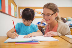 Pretty teacher helping pupil in classroom Stock Photography