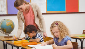 Pretty teacher helping pupil in classroom. At the elementary school Royalty Free Stock Photo