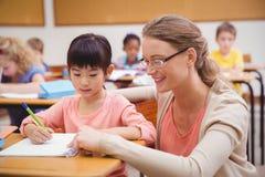 Pretty teacher helping pupil in classroom Stock Photo