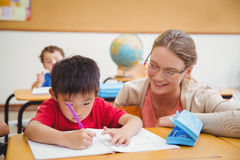 Pretty teacher helping pupil in classroom Royalty Free Stock Image