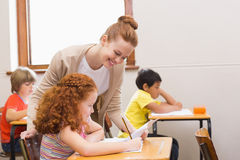 Pretty teacher helping pupil in classroom Stock Photos