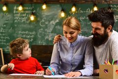 Pretty teacher helping pupil in classroom at the elementary school, Education activities in classroom at school happy Stock Photos