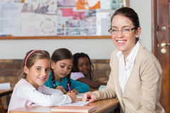 Pretty teacher helping pupil in classroom smiling at camera Royalty Free Stock Image