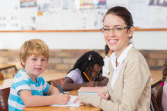 Pretty teacher helping pupil in classroom smiling at camera Stock Images