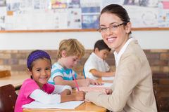 Pretty teacher helping pupil in classroom smiling at camera Stock Photo