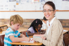 Pretty teacher helping pupil in classroom smiling at camera Stock Photography