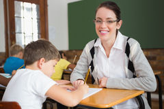 Pretty teacher helping pupil in classroom smiling at camera Royalty Free Stock Images