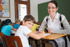 Pretty teacher helping pupil in classroom smiling at camera Stock Image
