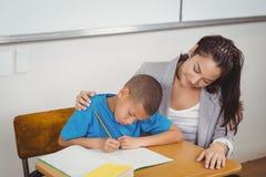 Pretty teacher helping pupil at his desk Stock Photos