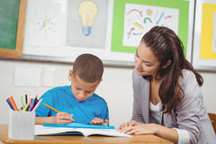 Pretty teacher helping pupil at his desk Stock Photography
