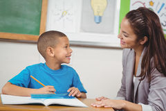 Pretty teacher helping pupil at his desk Stock Photo