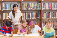 Pretty teacher helping pupils in library stock photography