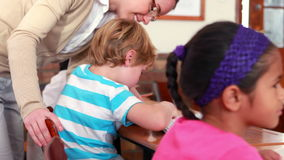 Pretty teacher helping schoolboy at his desk. In elementary school stock video footage
