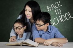 Pretty teacher helps students to study. Picture of pretty female teacher helping her students to read a book. Sitting in the class with text of back to school on Royalty Free Stock Image