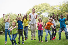 Pretty teacher jumping with pupils outside Royalty Free Stock Photos