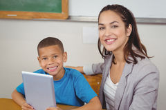 Pretty teacher and pupil with tablet at his desk. Portrait of pretty teacher and pupil with tablet at his desk in a classroom Stock Photography