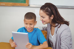 Pretty teacher and pupil using tablet at his desk Royalty Free Stock Photos