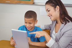 Pretty teacher and pupil using tablet at his desk Royalty Free Stock Images