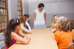 Pretty teacher showing laptop to pupils Royalty Free Stock Photo