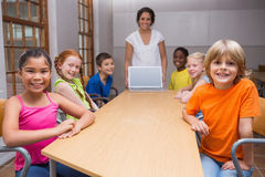 Pretty teacher showing laptop to pupils Stock Image