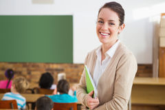 Pretty teacher smiling at camera at back of classroom. At the elementary school Stock Photography