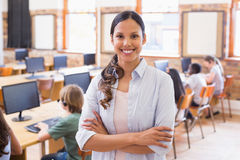 Pretty teacher smiling at camera at back of classroom Stock Image