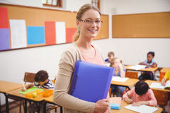 Pretty teacher smiling at camera while holding folder Royalty Free Stock Photography