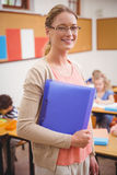 Pretty teacher smiling at camera while holding folder Stock Images