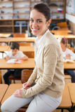 Pretty teacher smiling at camera at top of classroom Royalty Free Stock Image