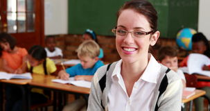 Pretty teacher smiling at camera at top of classroom. In elementary school stock footage