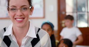 Pretty teacher smiling at camera at top of classroom. In elementary school stock video footage