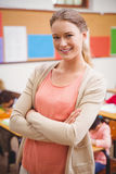 Pretty teacher smiling at camera at top of classroom Stock Photography