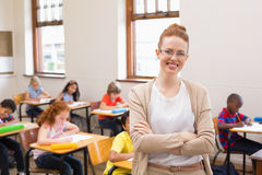 Pretty teacher smiling at camera at top of classroom Royalty Free Stock Images