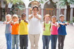 Pretty teacher standing with pupils in courtyard Stock Photo
