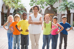 Pretty teacher standing with pupils in courtyard Royalty Free Stock Images