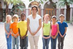 Pretty teacher standing with pupils in courtyard Stock Images