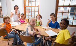 Pretty teacher standing with pupils at desk Stock Photo